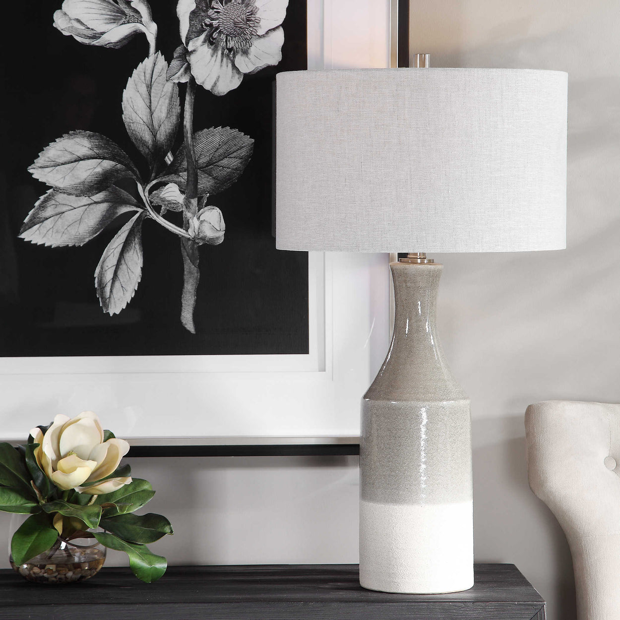 Showcasing a bohemian flair, this ceramic table lamp is finished in a glossy warm gray glaze that transitions to a heavily textured ivory bottom. The hardback drum shade is light gray linen with natural slubbing.
