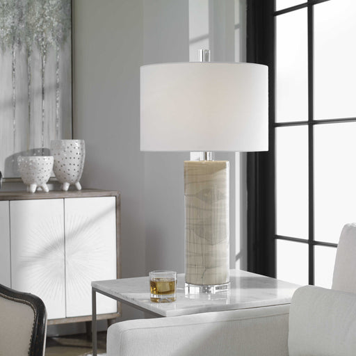 Modern in design, this ceramic table lamp showcases a neutral beige glaze with an abstract gray drip pattern, paired with elegant crystal details and polished nickel plated accents. The hardback drum shade is a white linen fabric.