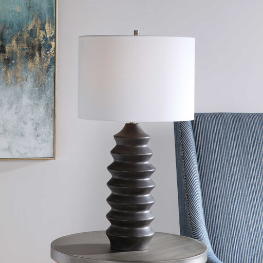 Showcasing a modern lodge style, this table lamp features a carved wood base finished in a rustic black stain exposing subtle wood grain. The lamp is paired with a round hardback drum shade in a white linen fabric.