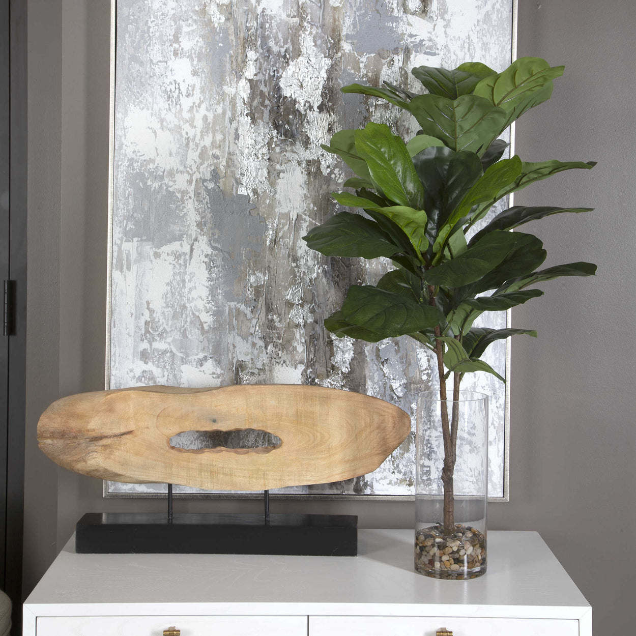 A staple across many design styles, this fiddle leaf fig branch is placed in a contemporary clear glass cylinder vase with natural stones and faux water.