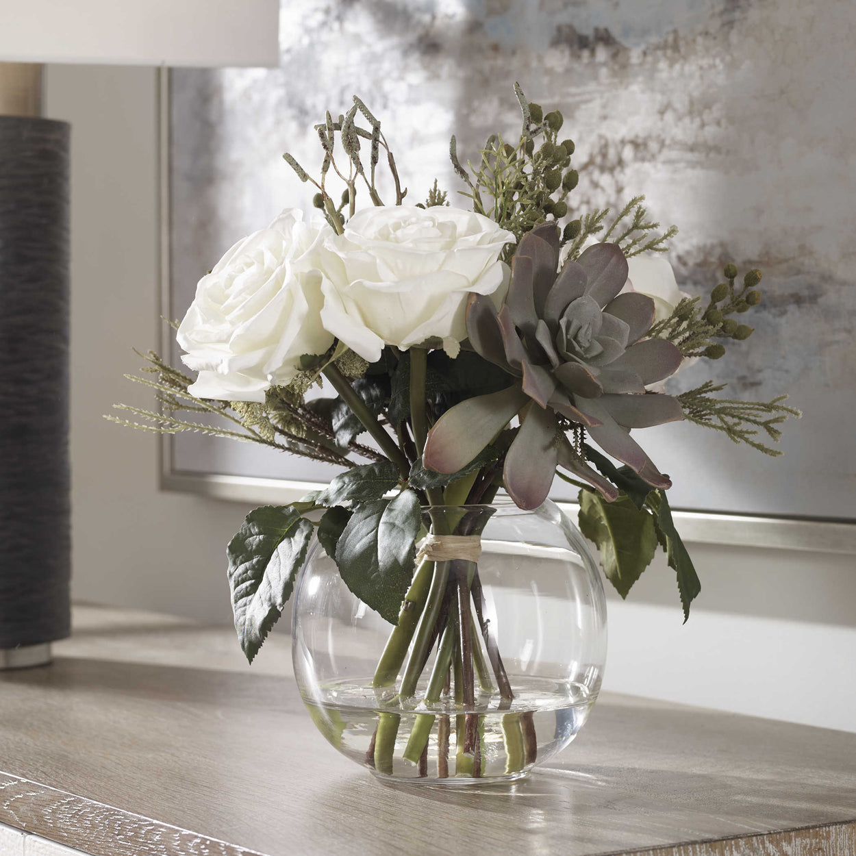 Modern floral bouquet features a unique mix of berries, greenery, seed pods, succulents and cream roses in a clear glass bud vase with faux water.