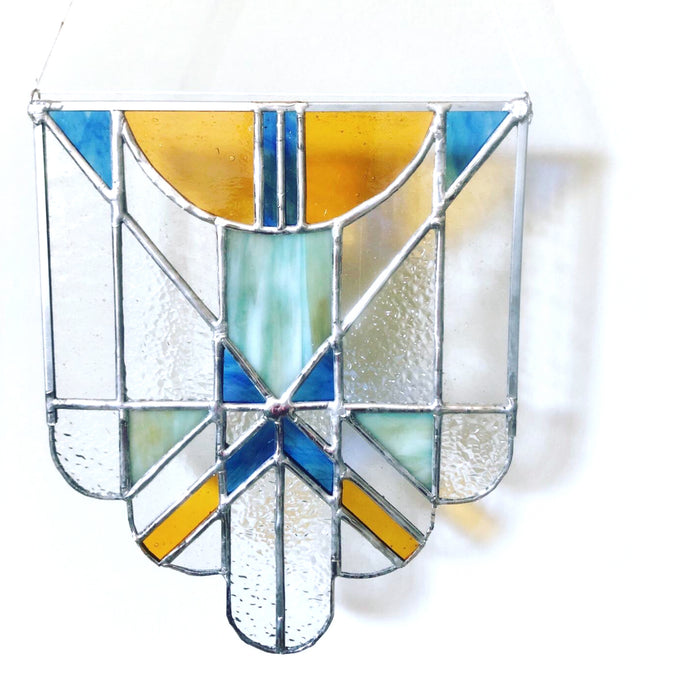 Handcrafted Art Deco style stained glass panel with scalloped edge in shades of blue and amber.
