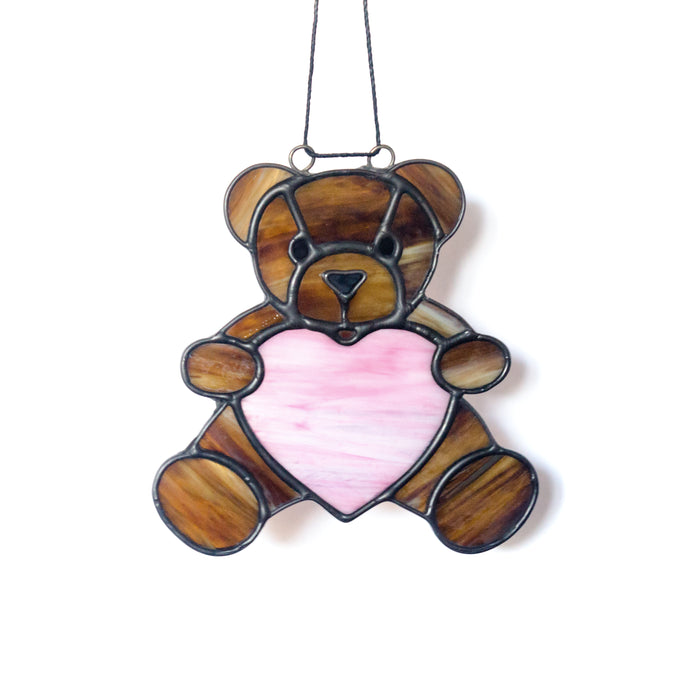 Hancrafted brown stained glass teddy bear hugging a pale pink heart.