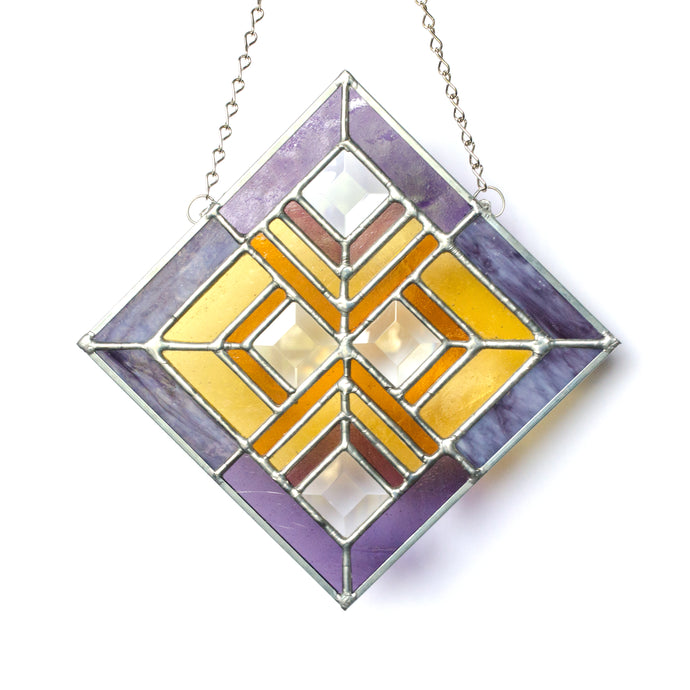 Stained glass panel in the prairie style of Frank Lloyd Wright featuring four clear square bevels with an updated color palette that includes purple, orange and amber.