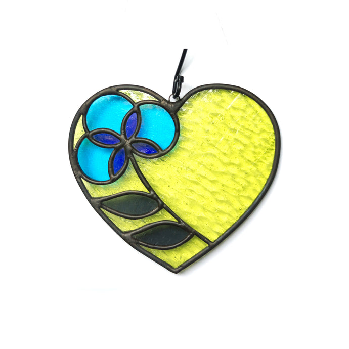 Heart-shaped stained glass suncatcher in highlighter yellow featuring flower in shades of blue and gray.
