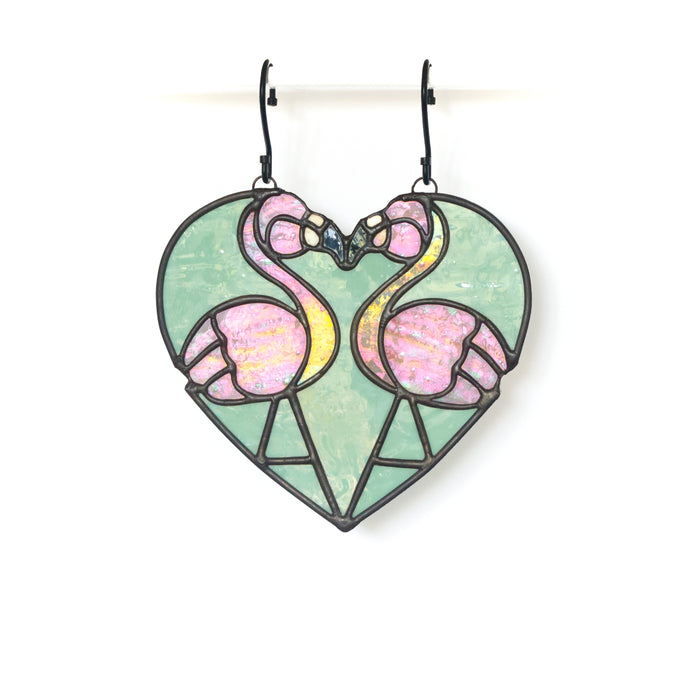 Stained glass heart in mint green featuring two iridescent pink flamingos with contrasting black finish.
