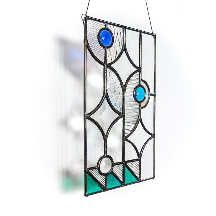 Handcrafted vertical rectangular stained glass panel featuring star-shaped glass bevels, a variety of clear textured glass, pops of iridescence and three faceted glass jewels in clear, cobalt and aqua.