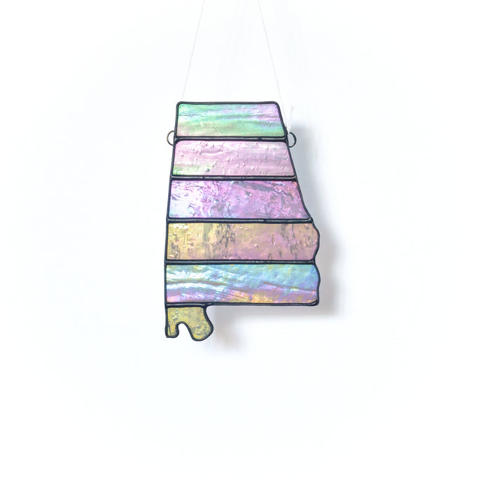 Handcrafted stained glass suncatcher in the shape of the state of Alabama in various shades of pastel iridescent glass with contrasting black border.