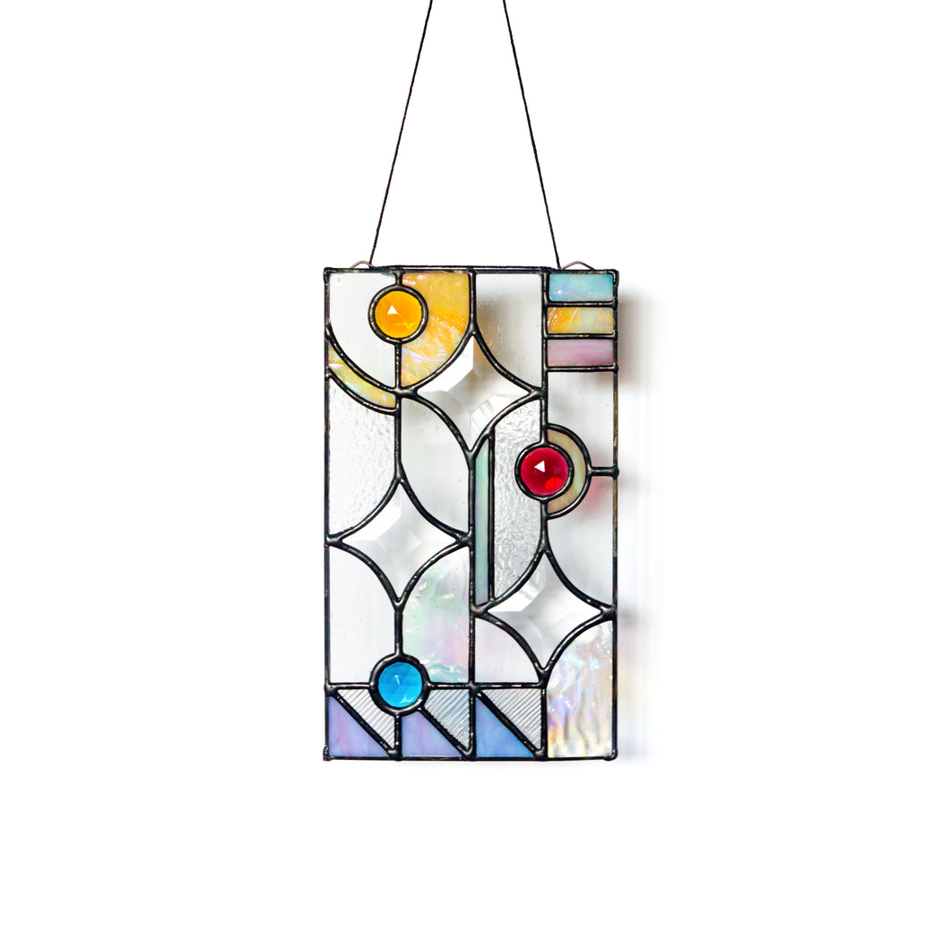 Handcrafted vertical stained glass panel with various textures; three clear star-shaped bevels; iridescent glass in shades of yellow, pink, blue and purple; and faceted glass jewels in aqua, pink and amber.
