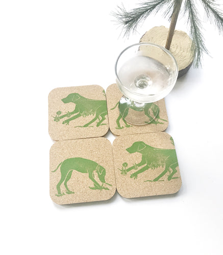 Cork coaster set with dog prints on each in green. One dog is laying down and the other is playing with a stick.