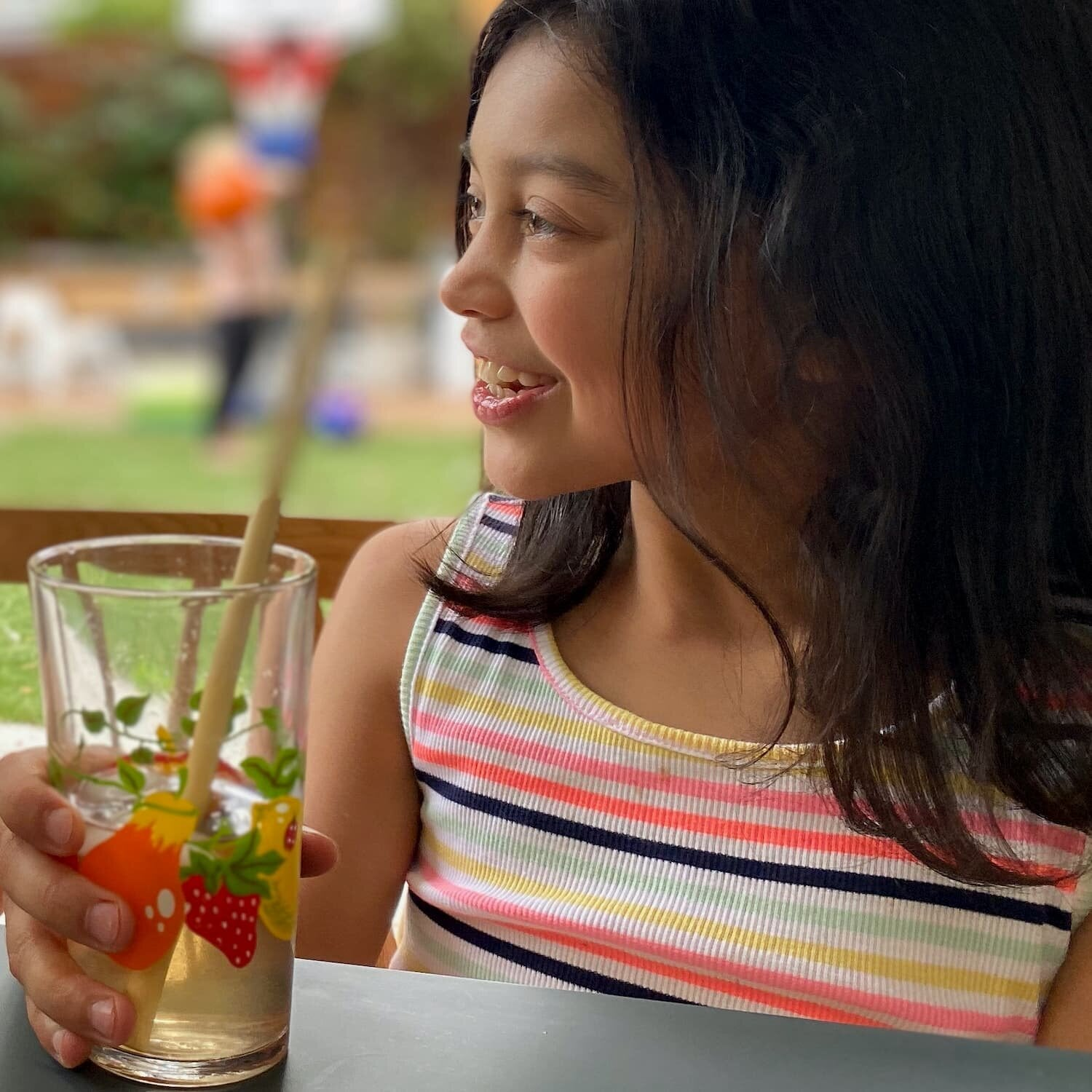 girl drinking iced tea from glass with straw