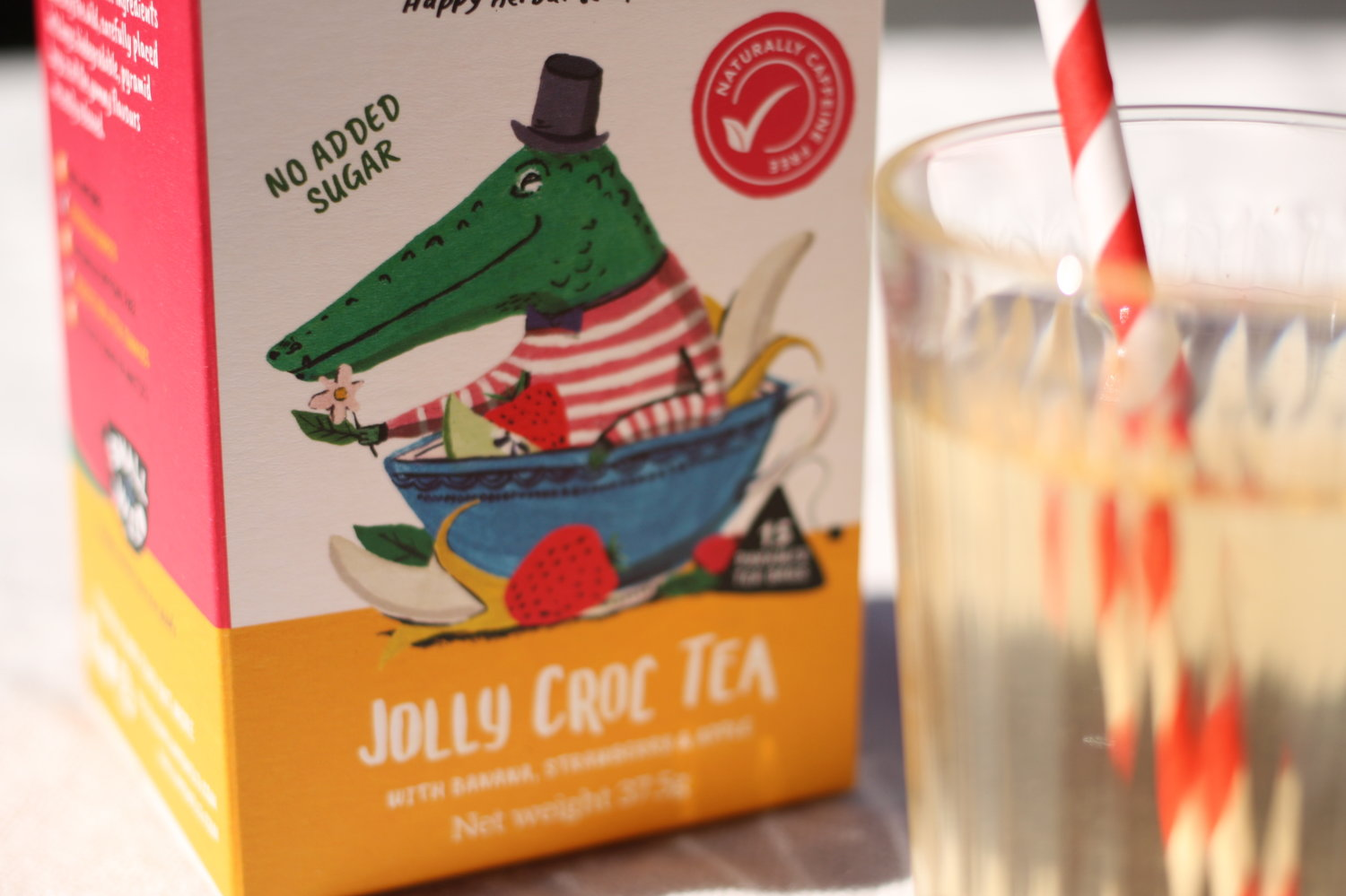 Jolly Croc fruit iced tea with banana and strawberry in glass with straw