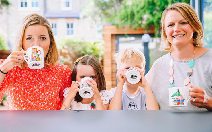 2 mums and 2 children drinking tea together at a kitchen table