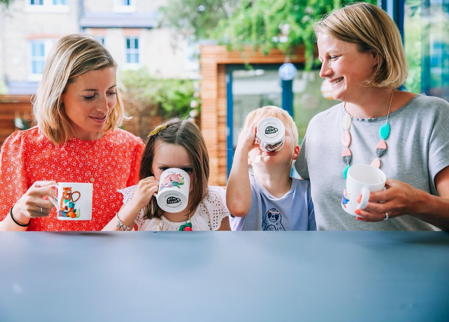 Two mums sharing a herbal tea with their children