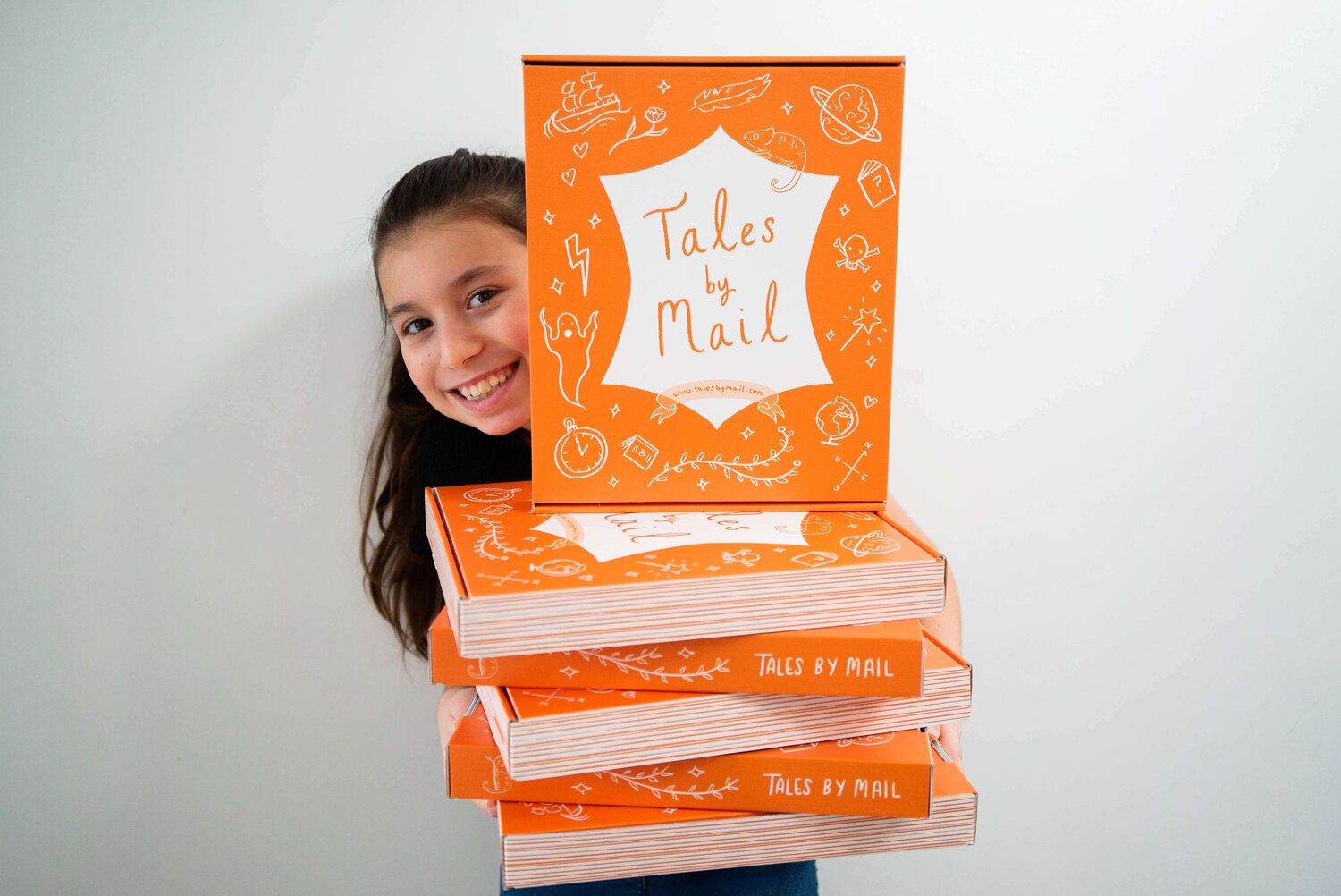 girl holding pile of book subscription boxes