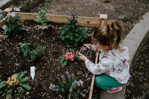 young girl taking photos of plants with phone