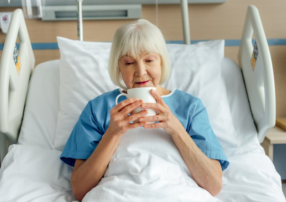lady in hospital bed drinking tea
