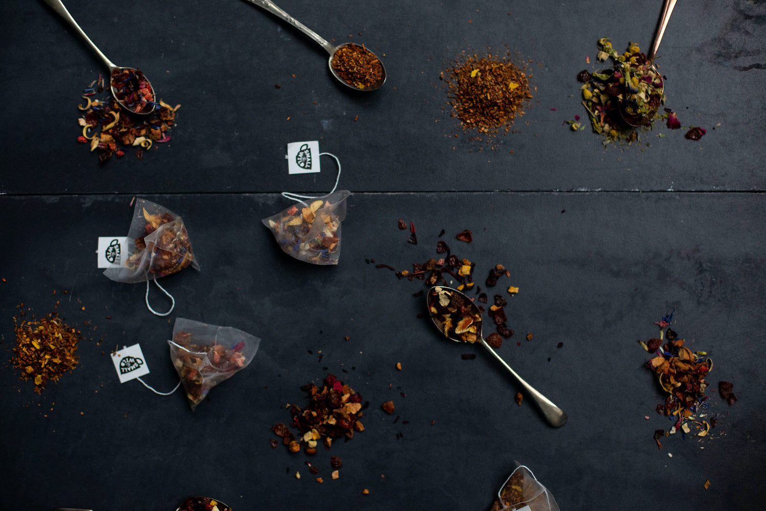 tea bags and loose tea on slate with teaspoons