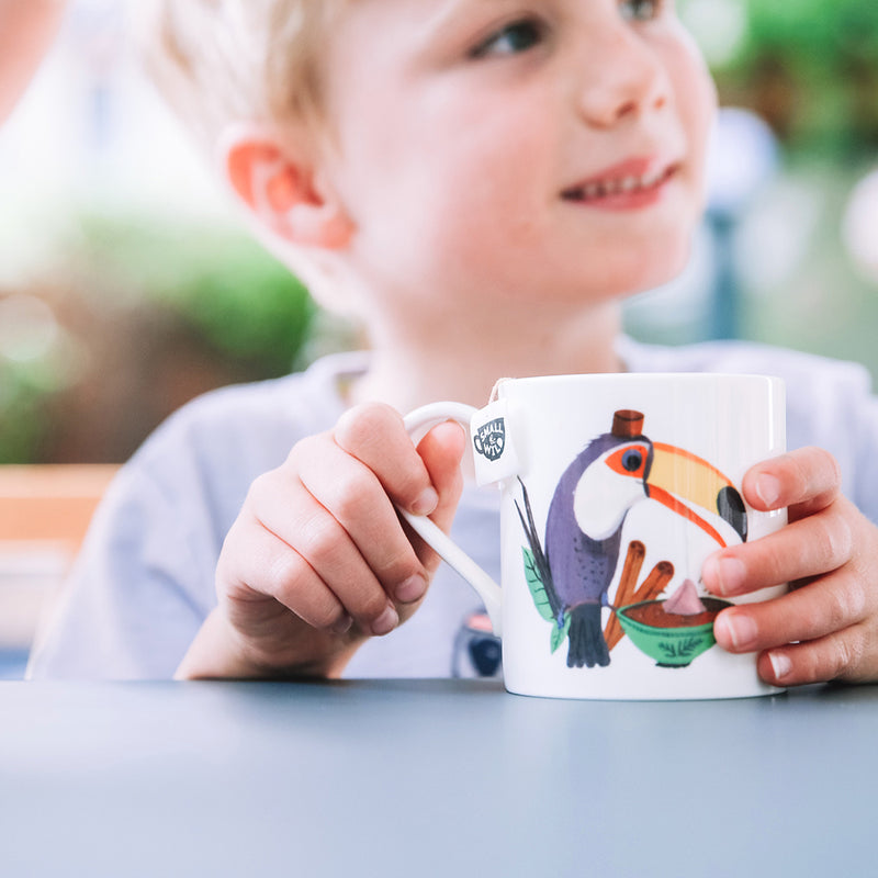 Child holding toucan mug