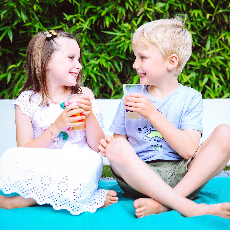 Kids drinking fruit tea over ice in summer