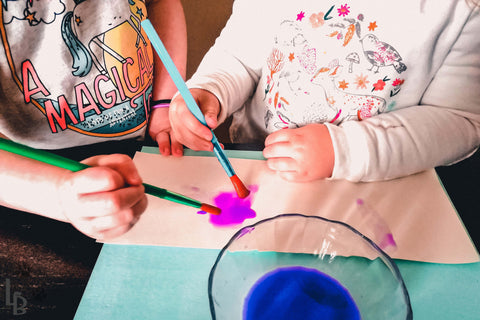 Children's writing activity shows young girls revealing text with purple paint