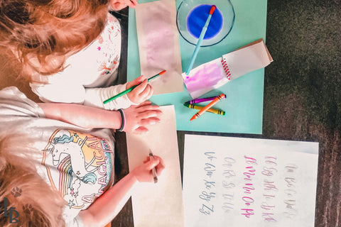 two girls writing their secret notes using white crayon and watery paint