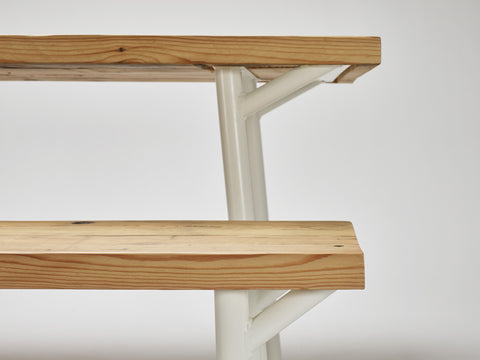 A close-up shot of the Trammel bench with its accompanying Trammel dining table