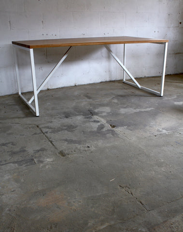 The modernist edge of an oak dining table with a steel frame