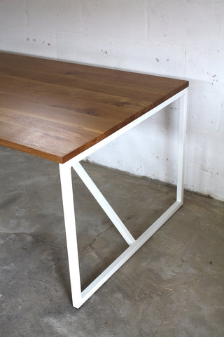 A combination of a modern steel frame and oak dining table top