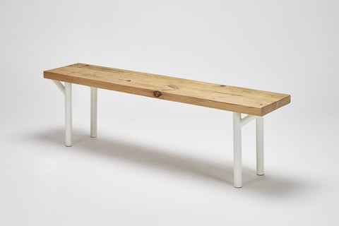 An angled view of our Trammel bench with its reclaimed wood top in pine and tube steel supports