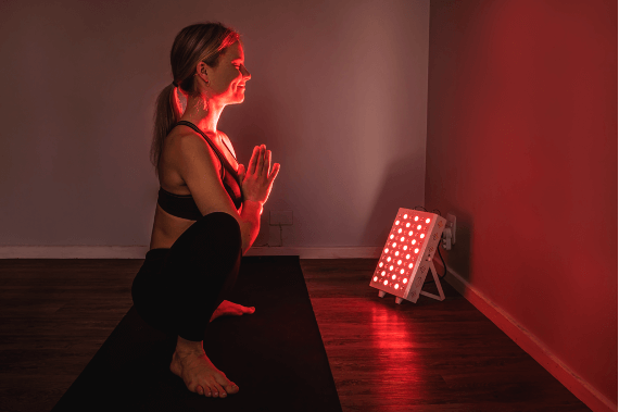 Girl in front of red light therapy device