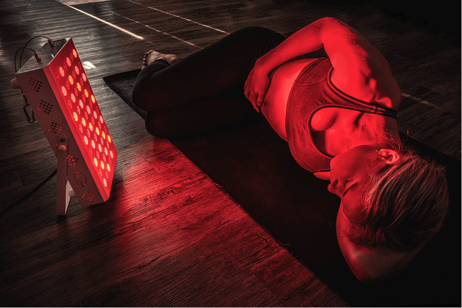 Girl lying next to red light therapy device