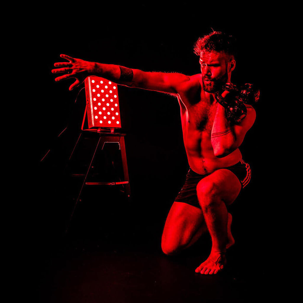 Man exercising in front of red light therapy device