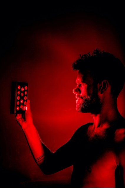 Man looking into red light therapy device