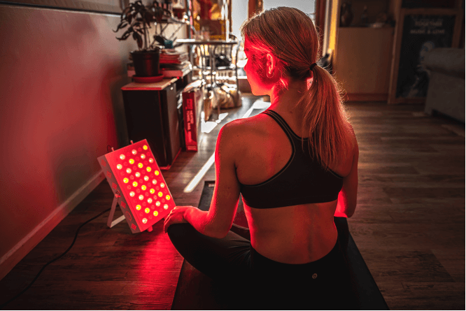 Woman using red light therapy device
