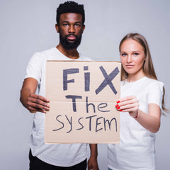 """A Black man and white woman holding a sign that says, """"Fix the System,"""" a nod to the Ally League's mission to unite against racism"""