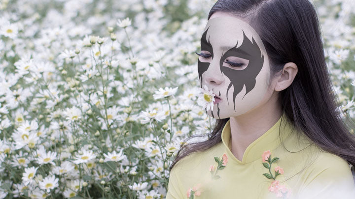 A girl wearing corpse paint smelling flowers