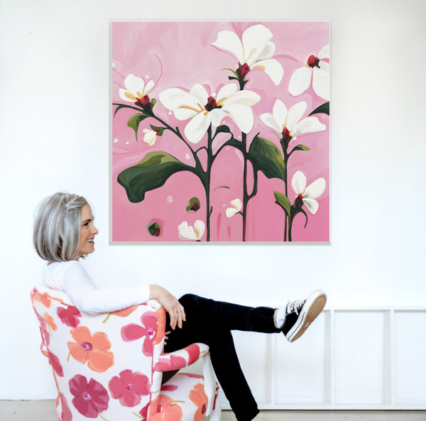Canadian abstract artist Susannah Bee sitting in a chair in front of 'pink white' from the In Bloom collection