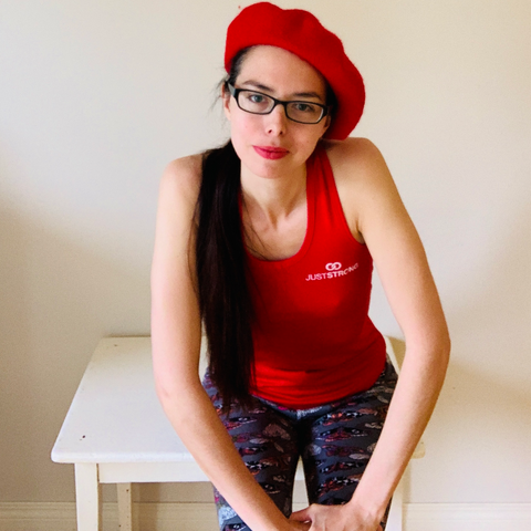A portrait of contemporary art activist Layla Messner wearing a red tank top and a raspberry red beret.