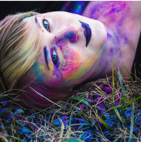 A portrait of designer, artist, activist Dani Redfern, with colorful paint powder on her face.