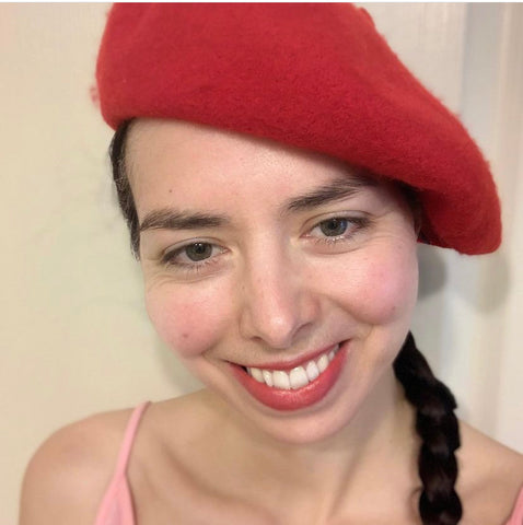 Headshot of contemporary art activist Layla Messner looking pretty in pink in a sundress and raspberry red beret.
