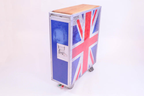 The Union Jack Airline Trolley is made from an original decommissioned hostess galley cart from China Southern made by Zodiac Aerospace. The trolley has been cleaned and vinyl covering have been added to both sides.  Each Trolley comes with a hard wood top in either in Oak, Elm or Cherry. The original galley cart wheels are still functional, so the trolley can be wheeled room to room. The foot brakes also still work.