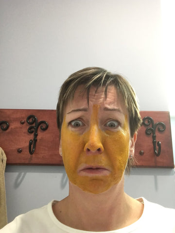 Woman with yellow face mask looking worried