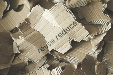 Torn cardboard that says reuse reduce