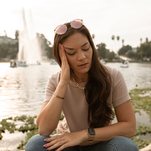 Woman sitting outside looking stressed