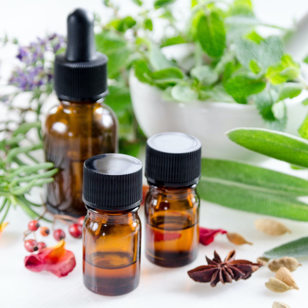 Three brown glass bottles of essential oils surrounded by herbs