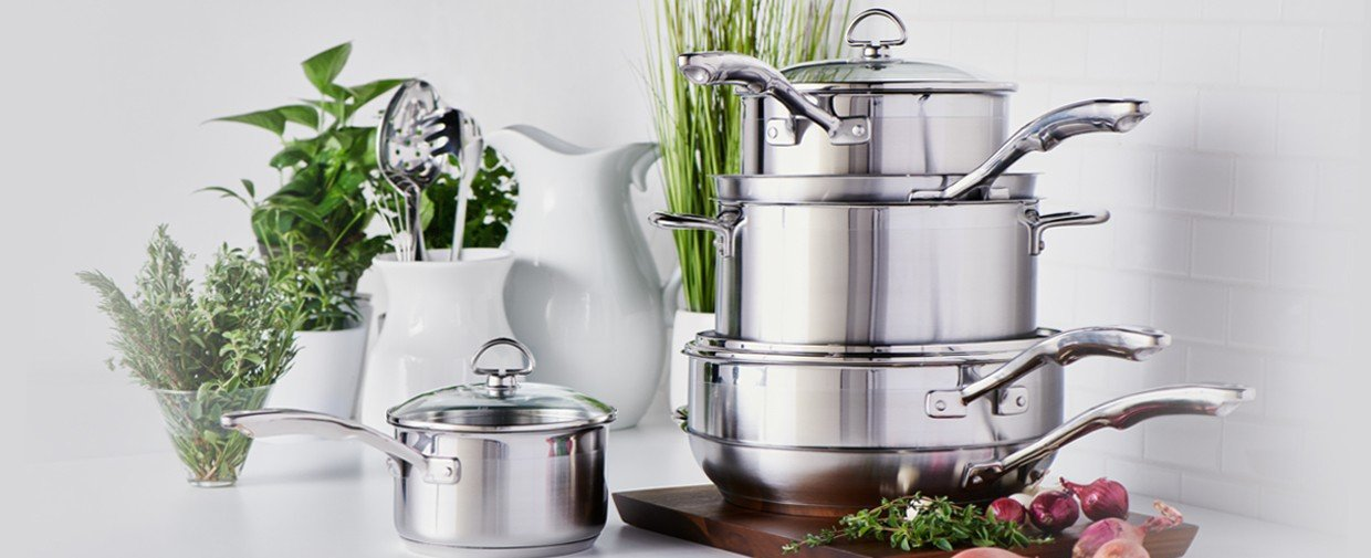 Multiple silver uncoated cookware stacked with fresh ingredients in white vases in the background