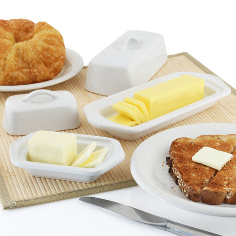 set of two white butter dishes with butter and bread