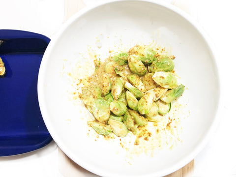 adding raw brussel sprouts to honey mustard mixture in bowl