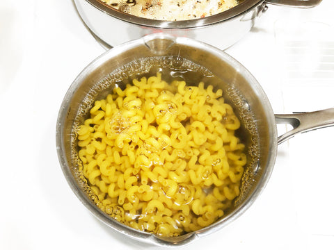 cooked pasta in id 21 stainless steel saupan with pour spout and strainer lid